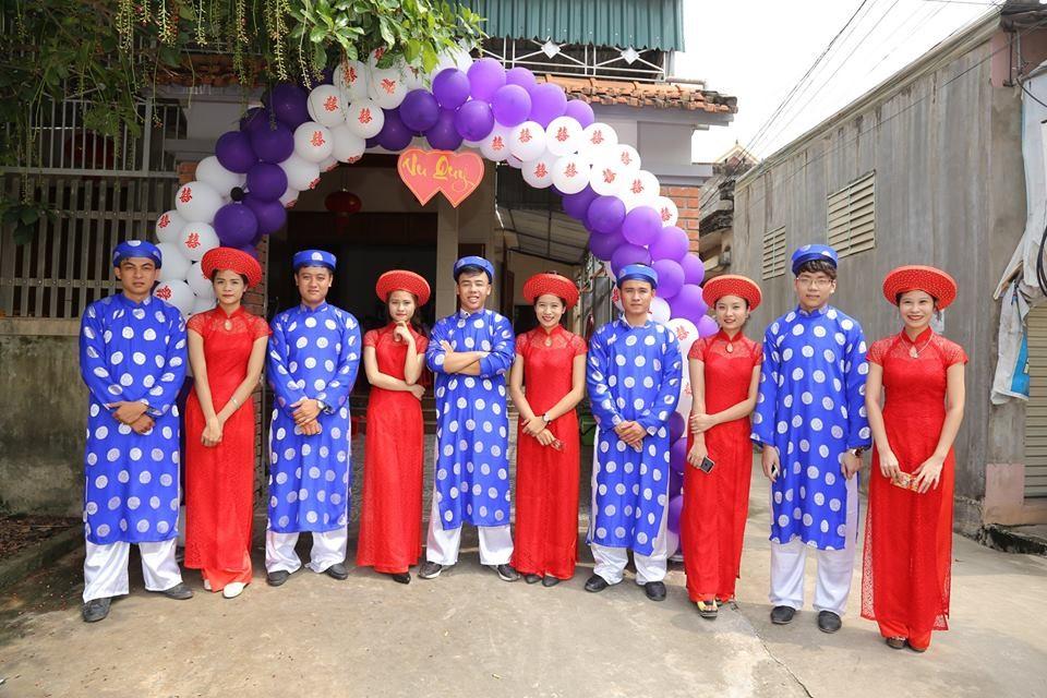 Phong cách chụp ảnh dập khuôn với đội bê tráp nam và nữ mặc áo dài truyền thống, đứng một hàng đan xen nhau trước rạp cưới.