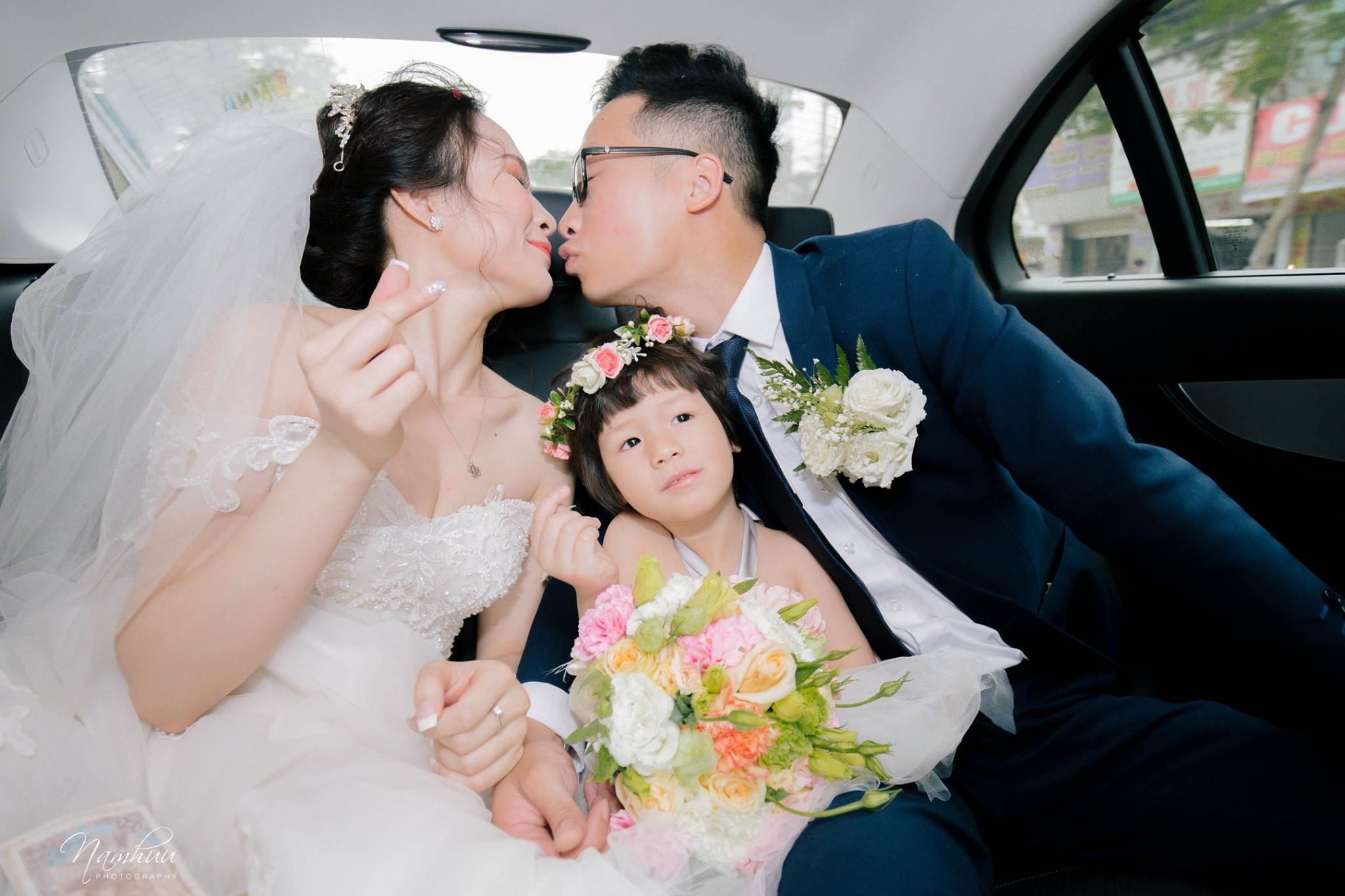 Cô dâu chú rế hôn nhau trong bức hình với em bé phù dâu mặt đầy cảm xúc ngồi giữa